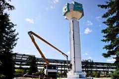 Ремонт часов башни Работники на час-столбце ремонта крана, часы на башне, краска, обновление, выполняют косметические ремонты стоковое фото