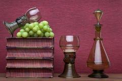 Ренессанс, бокал rummer, бутылка, старые книги и виноградины стоковая фотография