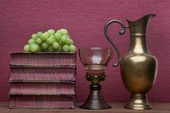 Ренессанс, бокал rummer, латунный carafe, старые книги и виноградины стоковое изображение