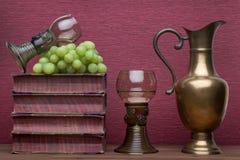 Ренессанс, бокал rummer, латунный carafe, старые книги и виноградины стоковые изображения rf