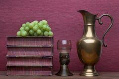 Ренессанс, бокал rummer, латунный carafe, старые книги и виноградины стоковое фото