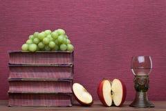 Ренессанс, бокал rummer, старые книги, яблоко и виноградины стоковая фотография rf