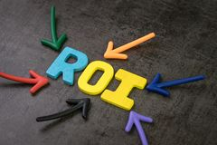 Рентабельность инвестиций ROI, критерий качества работы effeiciency дела, multi стрелок цвета указывая на слово ROI в центр стоковые изображения rf