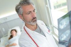 Рентгеновские снимки доктора рассматривая в комнате пациентов Стоковые Изображения