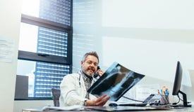 Рентгеновский снимок доктора рассматривая и говорить на телефоне Стоковое фото RF