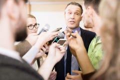 Репортеры интервьюируя бизнесмена Стоковое Изображение