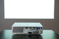 Репроектор цифров на таблице, с большим изолированным белым экраном на стене, никто стоковые фото