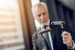 Респектабельный пожилой человек играя мини гольф в офисе Он смотрит 2 гольф-клуба и хочет выбрать одно из их Стоковое Изображение RF