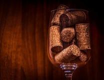 Ресторанное обслуживаниа, концепция партии: винтажное изображение конца-вверх бокала с пробочками на темной деревянной предпосылк Стоковое Фото