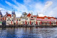 Рестораны и туристический офис Loetje Centraal на канале Damrak около центральной станции в старом центре города Амстердама Стоковое Изображение RF