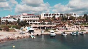 Ресторан гостиницы Кипра и белые шлюпки в Марине моря на пляже залива коралла Вид с воздуха гостиницы и туристических суден отдых акции видеоматериалы