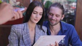 ресторан пар celebrat стеклянный красный детенышей вина Люди с меню делая заказ на кафе акции видеоматериалы