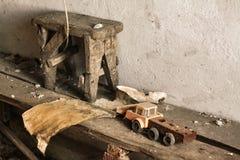 Ретро автомобиль игрушки, деревянная табуретка и часть пакостной бумаги, части покинули интерьер дома Забытое место стоковое фото rf