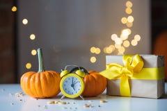 Ретро будильник с тыквами и подарочной коробкой около Fairy светов Стоковые Фото