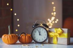 Ретро будильник с тыквами и подарочной коробкой около Fairy светов Стоковое Изображение