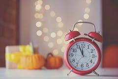 Ретро будильник с тыквами и подарочной коробкой около Fairy светов Стоковое Фото