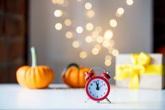 Ретро будильник с тыквами и подарочной коробкой около Fairy светов Стоковая Фотография
