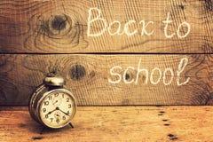 Ретро будильник на деревенской таблице и назад к надписи школы Стоковая Фотография RF