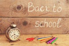 Ретро будильник на деревенской таблице и назад к надписи школы Стоковое Изображение RF