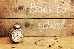 Ретро будильник на деревенской таблице и назад к надписи школы Стоковое Фото
