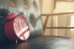 Ретро будильник на кожаной софе Стоковое фото RF