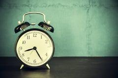 Ретро будильник на таблице с винтажной предпосылкой Стоковая Фотография