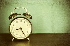 Ретро будильник на таблице с винтажной предпосылкой Стоковые Фото