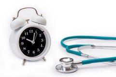Ретро будильник с изолятом o стетоскопа медицинских инструментов Стоковая Фотография