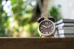 Ретро будильник указывая на часы ` 10:00 o с книгой Стоковое Изображение