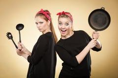 Ретро введенные в моду женщины имея потеху с аксессуарами кухни Стоковое Изображение RF