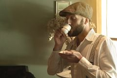 Ретро введенный в моду человек пробуя кофе в винтажной окружающей среде стоковая фотография rf