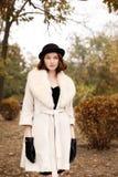 Ретро девушка гангстера в черной шляпе и пальто в осени паркуют Стоковые Фото