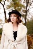 Ретро девушка гангстера в черной шляпе и пальто в парке осени смотрит в сторону Стоковая Фотография RF
