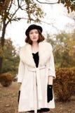 Ретро девушка гангстера в черной шляпе и пальто в парке осени смотрит в сторону Стоковые Изображения