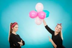 Ретро девушки подготавливая вечеринку по случаю дня рождения воздушных шаров Стоковые Изображения RF