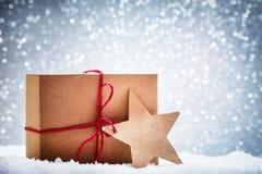 Ретро деревенский подарок рождества, присутствующий в снеге на предпосылке яркого блеска Стоковое Фото