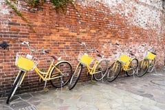 4 ретро желтых велосипеда паркуя красной кирпичной стеной Делить велосипеда стоковое изображение rf