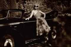 Ретро женщина стоя около автомобиля с откидным верхом стоковое фото rf