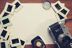 Ретро камера и некоторые старые фото на деревянном столе Стоковая Фотография