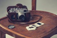Ретро камера и старые скольжения лежали на стуле Стоковое фото RF