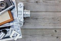 Ретро камеры, отрицательные фильмы и рамка фото на старом деревянном tabl Стоковое Фото