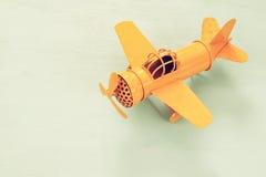ретро самолет игрушки желтого металла над деревянным столом Стоковые Фотографии RF
