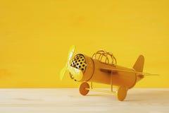 ретро самолет игрушки желтого металла над деревянным столом Стоковое фото RF