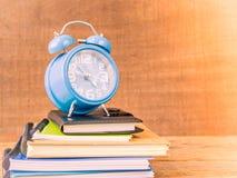 Ретро стиль будильника на стогах книг с предпосылкой деревянного стола Стоковое Изображение RF