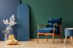 Ретро темно-синее кресло в элегантной, живущей комнате внутренней с космосом экземпляра на пустой зеленой и голубой стене стоковые изображения
