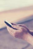 Ретро тонизированные руки взрослой женщины используя мобильный телефон outdoors Стоковые Фотографии RF