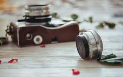 Ретро фильм и цветки фото крена камеры на белой деревянной предпосылке Стоковая Фотография