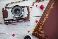 Ретро фильм и цветки фото крена камеры на белой деревянной предпосылке Стоковое Изображение