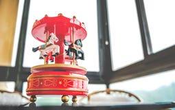 Ретро фильтрованный красный цвет коробки музыки игрушки тонизировал веселое идет carousel h круга Стоковое Фото