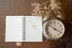 Ретро часы и примечание при белый цветок лежа на ржавой таблице Стоковые Изображения RF